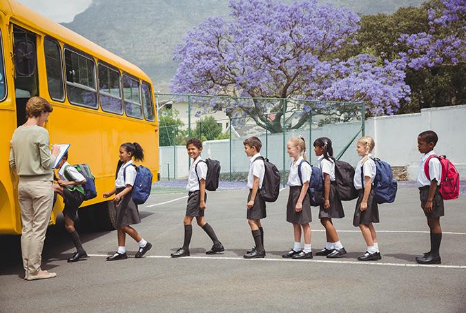 school children getting on a bus