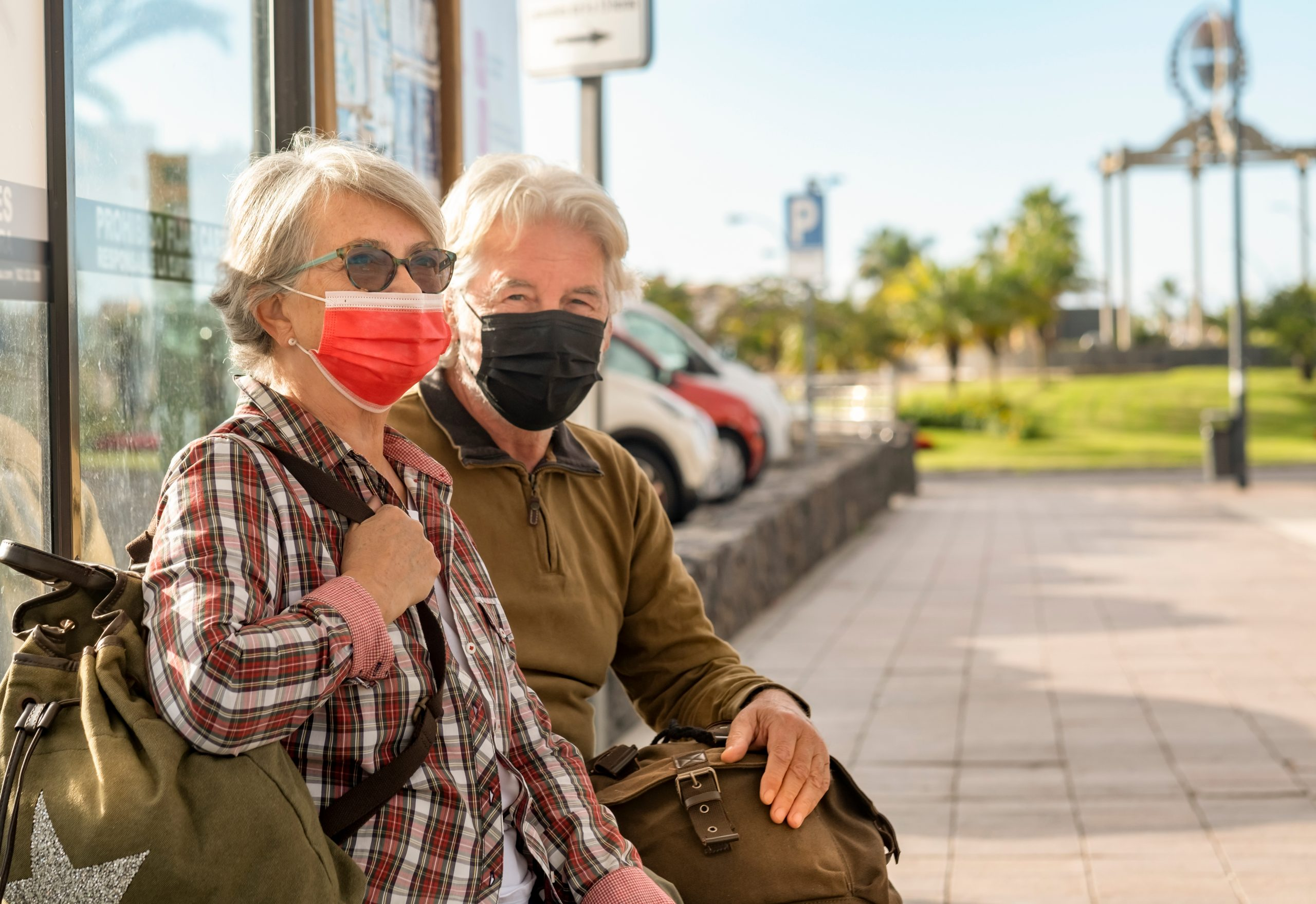 Elderly people waiting for a bus   wearing COVID mask